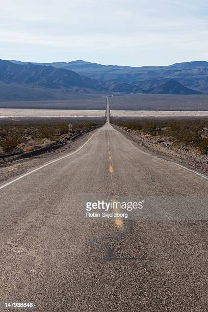 long strait desert road with yellow stripes. - robin skjoldborg stock pictures, royalty-free photos & images