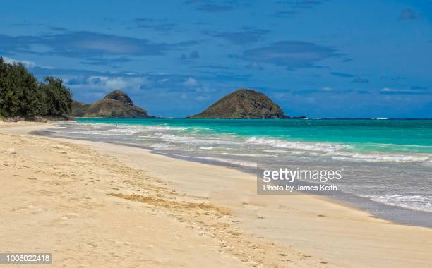 A long stretch of almost deserted beach on Oahu with Mokulua in the background.