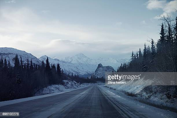 Long stretch of highway with snow covered mountain