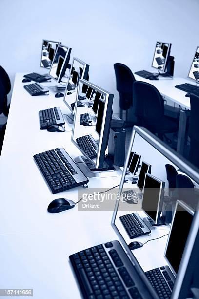 Lange Tische mit Computern mit Futter in einem blauen Farbton gehalten.