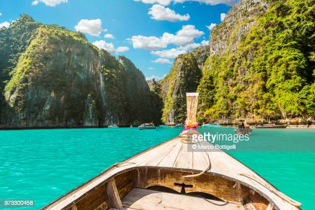 long tail boat at pileh lagoon, phi phi islands, thailand. - phi phi islands stock-fotos und bilder