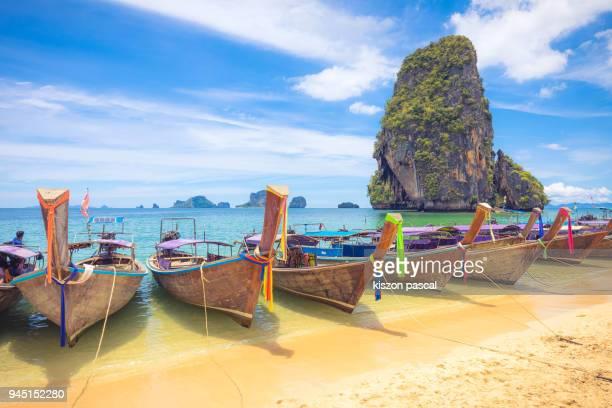 long tail boat on railay beach in krabi during a sunny day , thailand , asia - asiatisches langboot stock-fotos und bilder