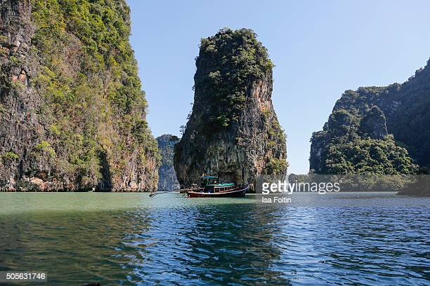 Long tail boats in front of Ko Tapu rock of James Bond Island in Phang Nga National Park on January 09 2015 in Ao Phang Nga National Park Thailand