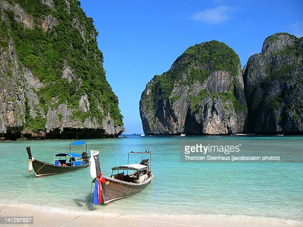 long tail boats on maya bay - phi phi islands stock-fotos und bilder