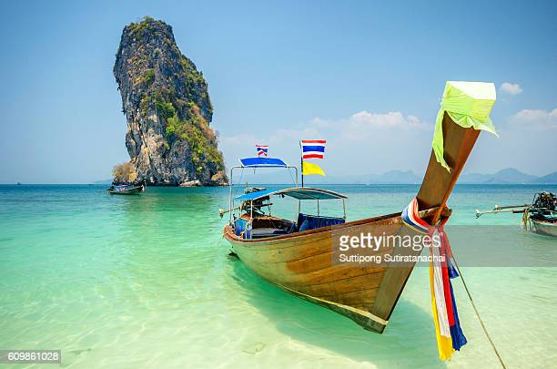 Long tailed boat Ruea Hang Yao on beautiful deep blue sea and blue sky in front of island background in Phuket Thailand