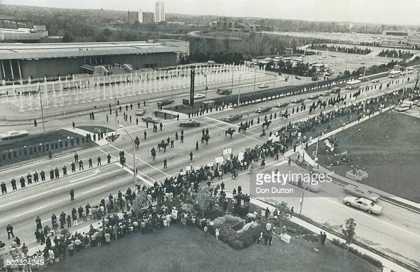 A long thin line of policemen mounted and on foot are streched along the median of Don Mills Rd yesterday waiting for the arrival of Soviet Premier...