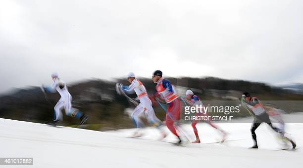 """Long time exposed picture shows athletes competing during the men's 15 kilometers pursuit classic style competition of the """"Tour de Ski"""" Cross..."""