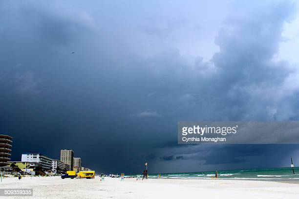 A long view of a dark and ominous summer thunderstorm hovering over a white sand beach Buildings and ice cream truck sit below the dark swirling...
