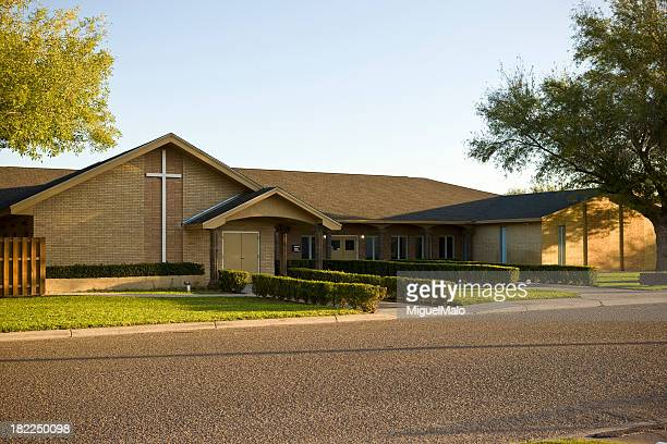 long view of the front of a brown brick church with a cross - church stock pictures, royalty-free photos & images
