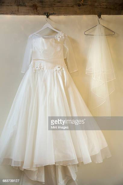 A long white wedding dress with full skirt, petticoats and veil on a hanger, hanging from a hook.