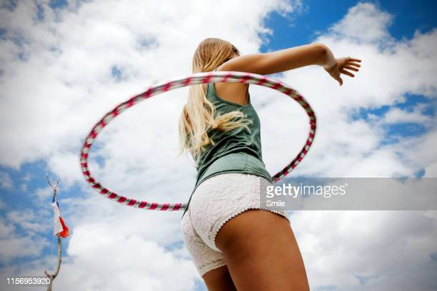 long woman hula hooping on blue cloudy skies - fessier femme photos et images de collection
