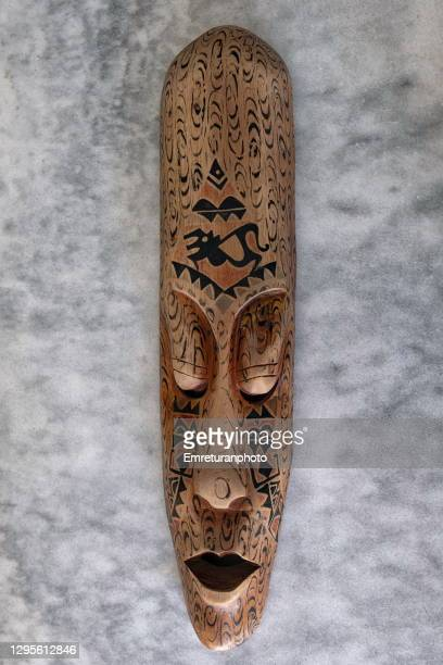 long wooden carved african mask on a granite surface. - emreturanphoto stock pictures, royalty-free photos & images