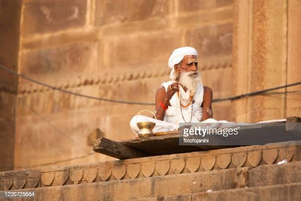 a long-bearded sadhu, or holy man sitting on the streets of varanasi - fotofojanini foto e immagini stock