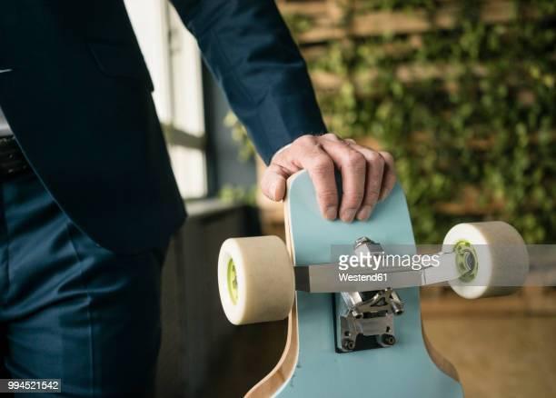 longboard in businessman's hand - longboard skating stock-fotos und bilder