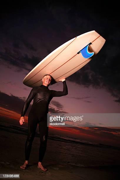 Longboard na cabeça de surfista ao pôr do sol