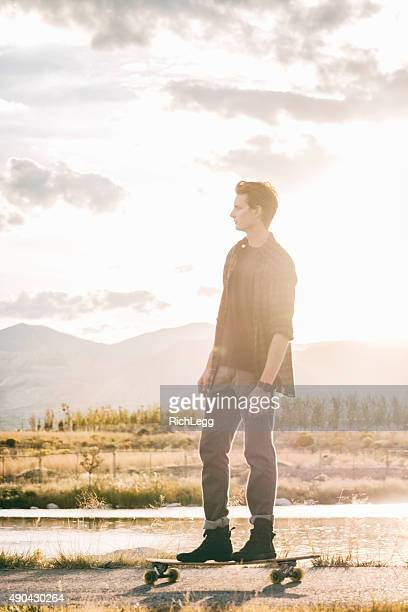 longboarder at sunset - rich_legg stock pictures, royalty-free photos & images