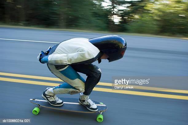 Longboarder on road, side view