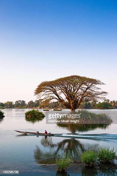 A longboat cruises through calm waters.