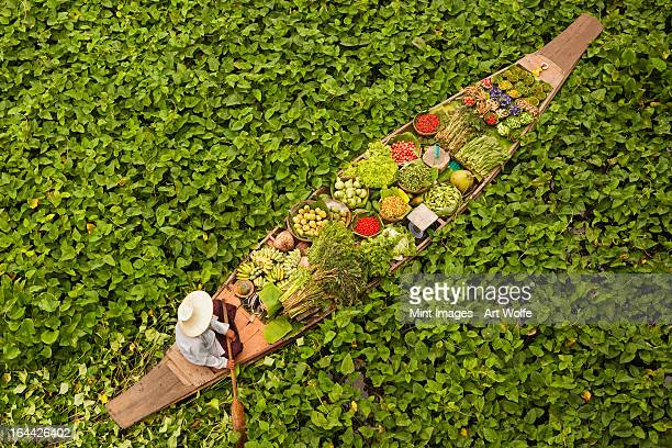 a longboat or dug out canoe, laden with food and fresh produce, at a floating market on a klong in thailand. - floating market stock photos and pictures