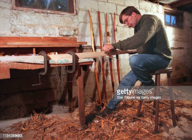 Longbow hunting Bob Usgaard sits amid a pile of wood shavings as he works on widling down a piece of wood into a long bow This in his basement of his...