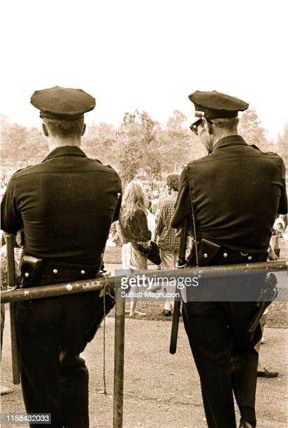 Long-haired couple seen through the silhouettes of two police men at the 1st Elysian Park Love-In on March 26, 1967 in Los Angeles, California.