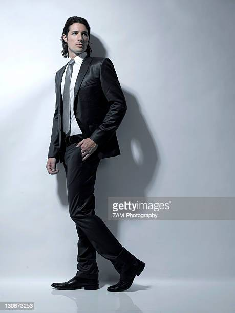 Long-haired man in his early thirties wearing a suit, fashion shoot