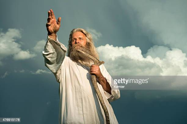 long-haired prophet gesturing in front of dramatic sky - god stock pictures, royalty-free photos & images