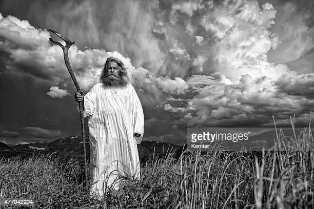 long-haired prophet gesturing in front of dramatic sky
