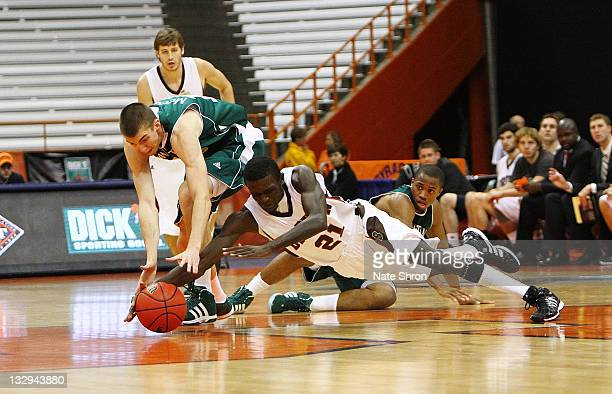 Longi Yiljep of the Brown Bears dives to reach the ball against Ryan McCoy the Manhattan Jaspers during the NIT Se ason Tipoff game at the Carrier...