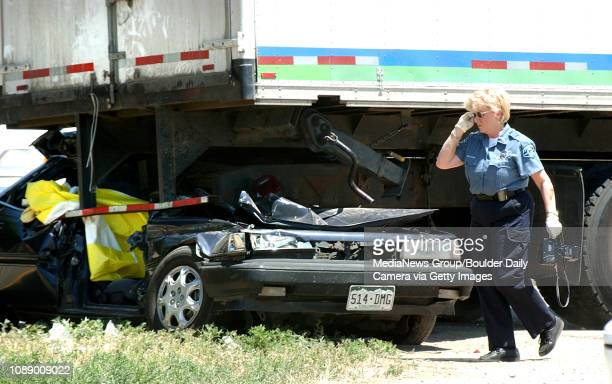 Longmont Police Investigator Sonny Green walks around a Toyota Camry which is wrapped under the rear end of transport truck at the scene of a fatal...