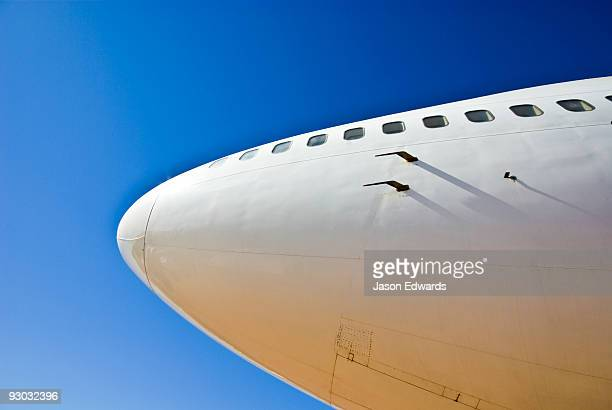The nose cone of a 747 passenger aircraft soars into a clear blue sky.