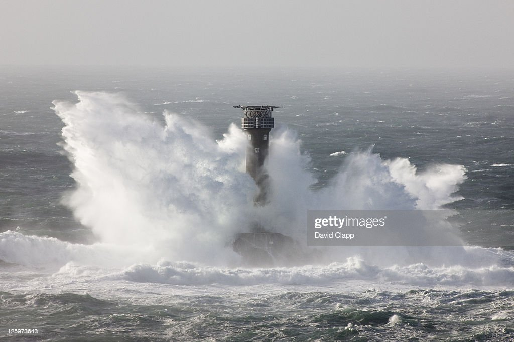 Longships Lighthouse being pounded by waves during an Atlantic storm. Lands End, Cornwall, England, UK : Stock Photo
