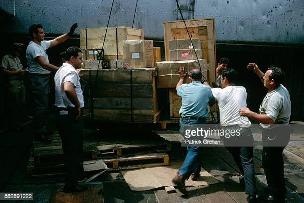 Longshoremen load cargo on to a freighter in New York City Harbor