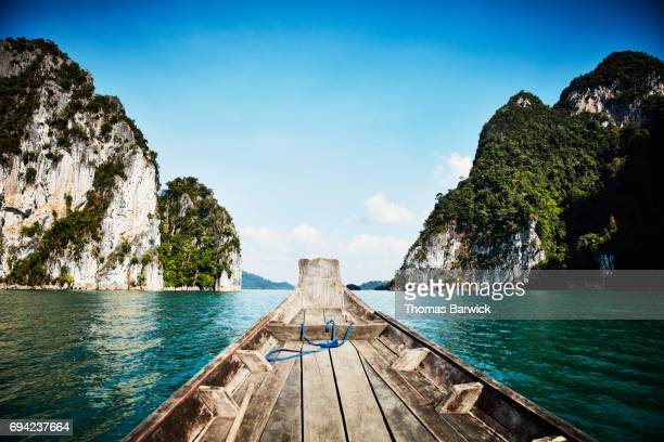Long-tail boat navigating Cheow Lan Lake in Khao Sok National Park Thailand