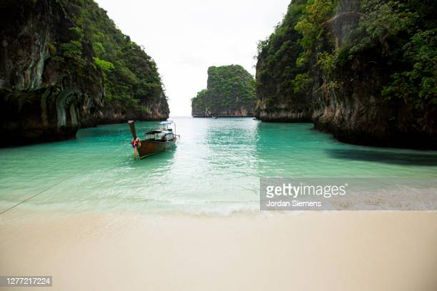 a long-tail boat parked on a secluded beach in thailand. - asiatisches langboot stock-fotos und bilder