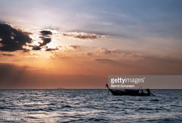 longtail boat sunset - bernd schunack stock pictures, royalty-free photos & images