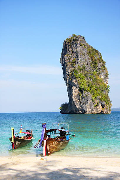 Longtail boats and limestone outcrop at beach of Poda Island.