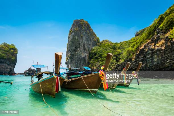 longtail boats moored on emerald green shore - phi phi islands stock-fotos und bilder