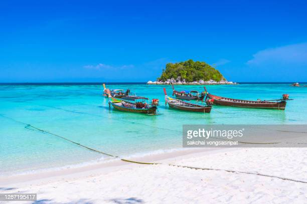 longtail boats on beach against sky at koh lipe island, thailand, asia - asiatisches langboot stock-fotos und bilder