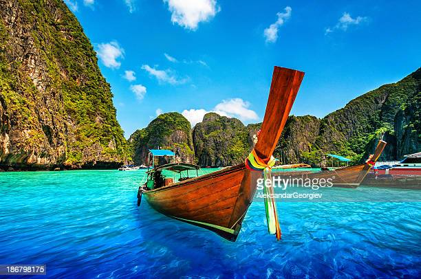a longtail wooden boat at maya bay, thailand - phuket province stock pictures, royalty-free photos & images