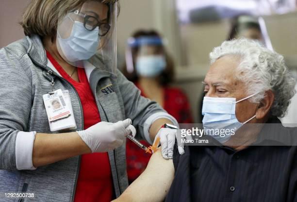 Long-term care patient Carlos Alegre receives the Pfizer-BioNTech COVID-19 vaccine from licensed vocational nurse Virgie Vivar at Birch Patrick...