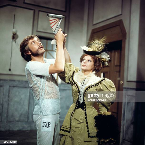 Loni von Friedl greift nach der Pistolenattrappe in Joachim Ansorges Hand in Ein Klotz am Bein, Regie: Stanislav Barabas, 1976.