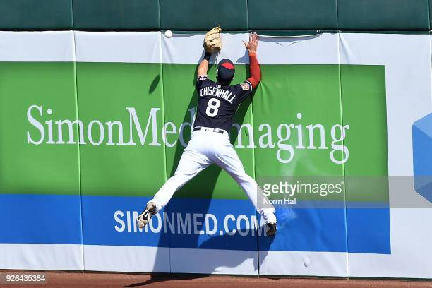 Lonnie Chisenhall of the Cleveland Indians collides with the right field wall while attempting to make a leaping catch on a double hit by Roughned...