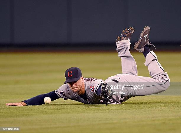 Lonnie Chisenhall of the Cleveland Indians dives for a ball off the bat of Carlos Perez of the Los Angeles Angels during the third inning at Angel...