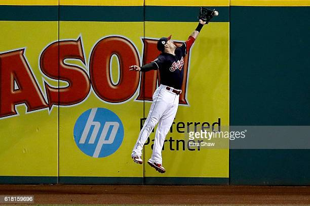 Lonnie Chisenhall of the Cleveland Indians is unable to make a catch on a ball hit by Willson Contreras of the Chicago Cubs in the ninth inning in...