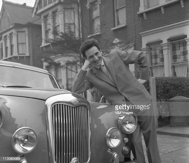 Lonnie Donegan posed leaning on the bonnet of a Riley TwoPointSix car on a residential street 1959