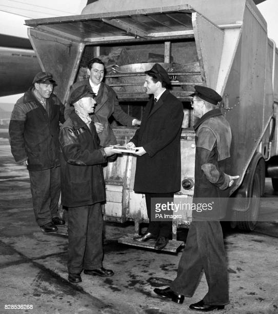 Lonnie Donegan receives a Gold Disc for 'My Old Man's a Dustman' at London Airport from dustman while standing on a dustman's lorry