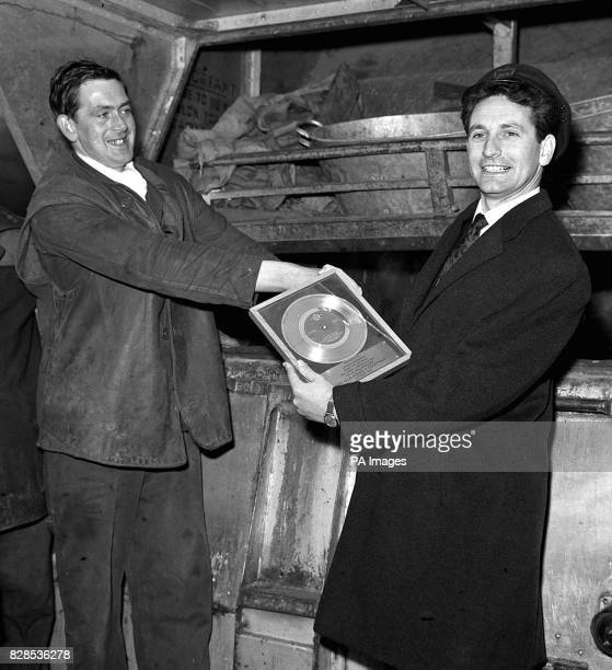 Lonnie Donegan receives a Gold Disc for 'My Old Man's a Dustman' from a dustman standing on a dustcart at London Airport