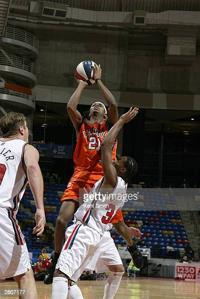 Lonnie Harrell of the Columbus Riverdragons shoots against Junie Sanders of the Fayetteville Patriots December 12, 2003 at the Crown Coliseum in...