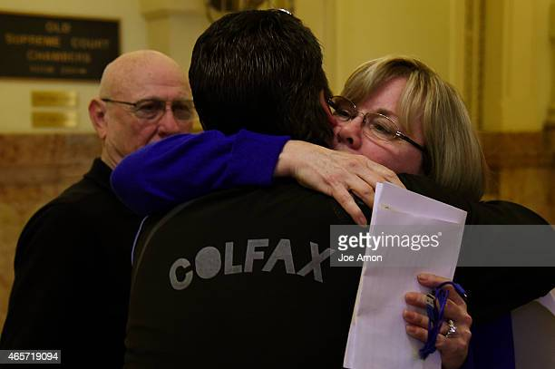 Lonnie Phillips watches as his wife Sandy hugs Dave Hoover after they gave testimony on the family members they lost during the theater shooting's in...